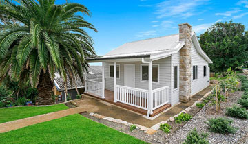 white granny flat with white picket fence